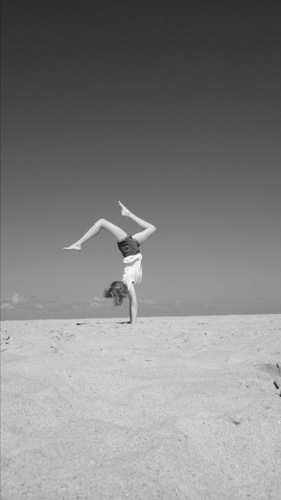 handstand on sandy beach