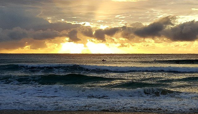 lone surfboard rider in the morning surf
