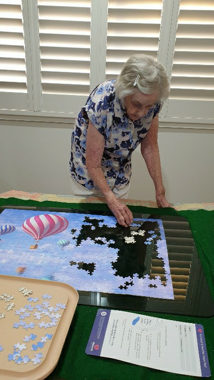 old woman completing puzzle